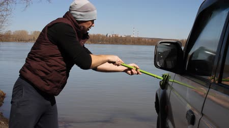 prát : a man washing an SUV with a MOP and a rag from the bucket on the river