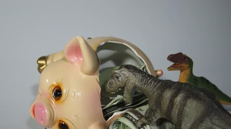 zingeving : Two carnivorous dinosaurs T Rex and VelociRaptor killed a pig coin box and ate its insides capital, Finance in the pig year 2019. Allegory Stockvideo
