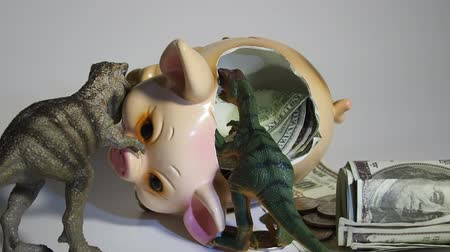 kazık : Two carnivorous dinosaurs T Rex and VelociRaptor killed a pig coin box and ate its insides capital, Finance in the pig year 2019. Allegory Stok Video
