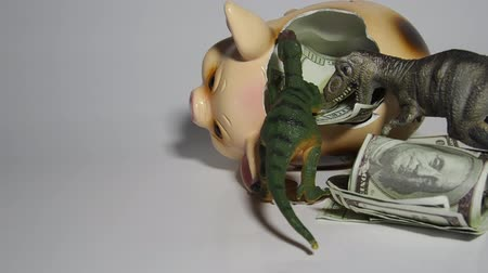 significado : Two carnivorous dinosaurs T Rex and VelociRaptor killed a pig coin box and ate its insides capital, Finance in the pig year 2019. Allegory Stock Footage