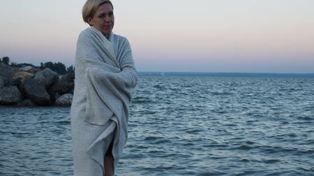 warms : woman blonde one is on the beach wrapped in a blanket and sad. Shes cold, her eyes on the sea. Slow motion video