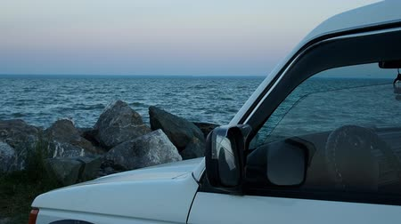 obstacles : car SUV white against the evening sea and a pile of large stones close-up Stock Footage