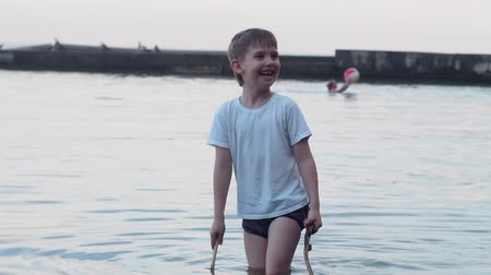 pływanie : the boy walks into the water and screams with surprise that the water is cold. He has two sticks in his hands and his sister plays next to him