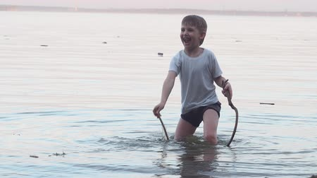 caráter : the boy stands in the sea and plays with water sticks in his hands, rejoices and laughs, sticks in the water Stock Footage