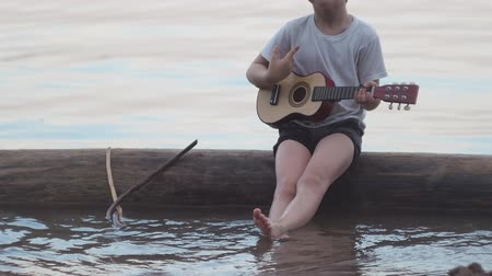 compositor : little boy playing guitar sitting on a log in the sea. He smiles and sings merry songs