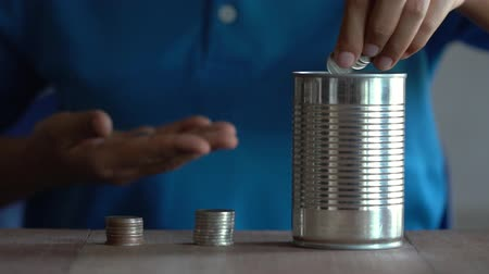 Woman wearing a blue shirt is drop a coin into a old can on a brown wooden table. The concept of saving money.
