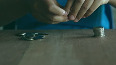 Woman wearing a blue shirt is are stacking coins on a brown wooden table. The concept of saving money.