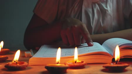 Dolly woman reading a book with the light of many candles in small pottery container. The concept of education or energy saving.