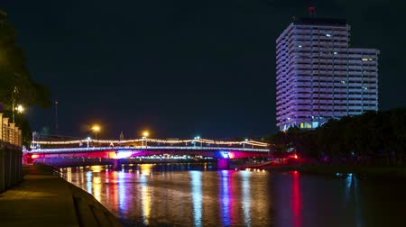 Time lapse riverside building and the car is crossing the bridge in night at Chiangmai Thailand. Stok Video