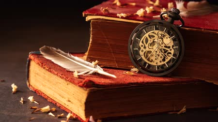 eight : Time lapse winding pocket watch on old books with feathers and dried flower petals on the marble table in darkness and morning light.