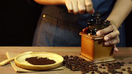 Slow motion womens hands are grinding coffee beans on a wooden table. Dostupné videozáznamy