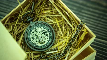 minutos : Time lapse Pocket watch winder on natural wheat straw in a wooden box. Concept of vintage or retro gift. Stock Footage