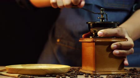 Dolly zoom womens hands are grinding coffee beans on a wooden table. Dostupné videozáznamy