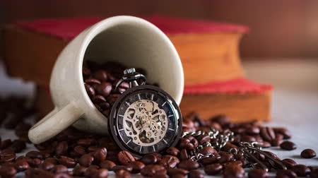 Time lapse pocket watch and coffee cup on coffee seed and old book on wooden table. Copy space for text. The concept of time to read books.