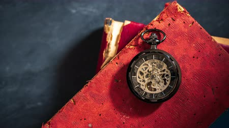 Time lapse pocket watch on old book. Top view and copy space for text. Concept of time and education.