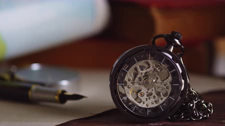 Pocket watch with old books and pen with paper map on the table by the window. Concept of travel planning. Dostupné videozáznamy