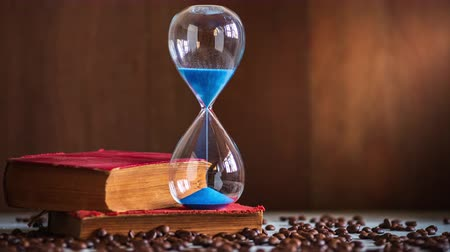 Time lapse sand clock on the old book and coffee seed on wooden table. Copy space for text. The concept of time to read books.