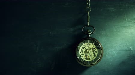 Time lapse pocket watch hanging on black chalkboard and sunlight in morning. Concept of time and education.