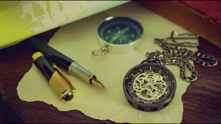Time lapse pocket watch with old books and pen with paper map on the table by the window. Concept of travel planning.