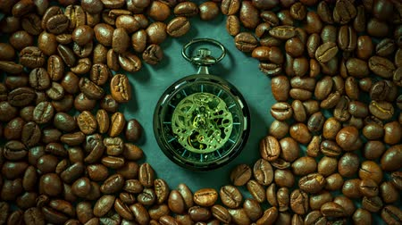 Time lapse pocket watch among coffee bean on table in morning. Concept of coffee time. Stok Video