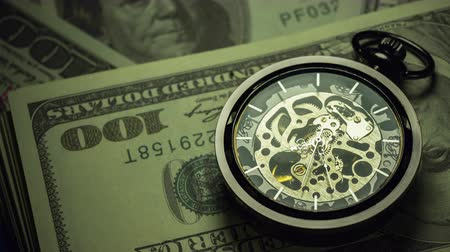 minutos : Time lapse pocket watch on dollar banknote stacking in darkness. Concept of Time is money or Business.