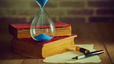 Time lapse sand clock with old books and pen with old paper on the wooden table. Concept of travel planning.