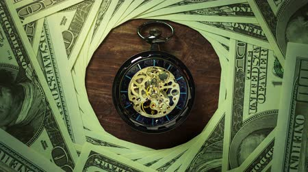 積み重ね : Time lapse pocket watch on the floor among dollar banknote stacking in darkness. Concept of Time is money or Business. 動画素材
