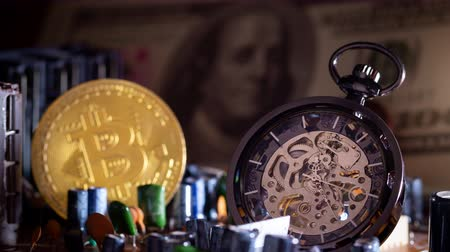 Time lapse pocket watch and gold bitcoin with dollar banknote on computer mainboard in darkness background. Stok Video