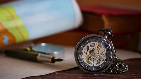 minutos : Time lapse pocket watch with old books and pen with paper map on the table by the window. Concept of travel planning.