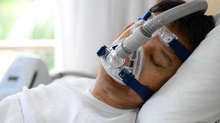 respiração : Close up of man upper body lying in bed wearing cpap mask breathing and sleeping smoothly without snoring,side view . Obstructive sleep apnea therapy.