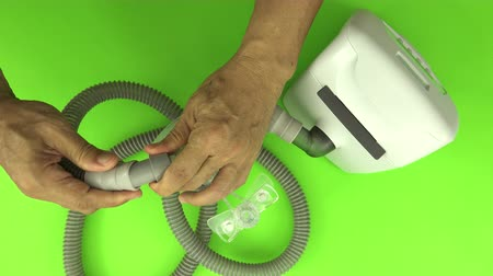 パネル : Man hands assembling tube to a cpap mask white green screen,top view. CPAP routine maintenance.