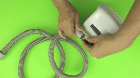 パネル : Man hands assembling tube to a cpap machine white green screen, top view. CPAP routine maintenance.