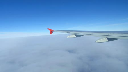 airplane engine : Wing of airplane flying above the clouds in the sky Stock Footage