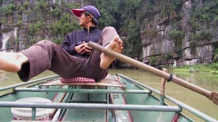 tam coc caves : TAM COC, NINH BINH, VIETNAM - FEBRUARY 21: Unidentified paddler in Tam Coc paddle a tourist boat with his feet. Ninh Binh is visited every year by thousands of tourists. On Feb 21, 2013, Tam Coc, Vietnam Stock Footage