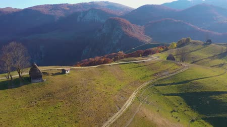 assombro : Aerial drone 4k view of autumn countryside mountain landscape with wooden houses, thatched roof and dirt road in Transylvania, Romania Stock Footage