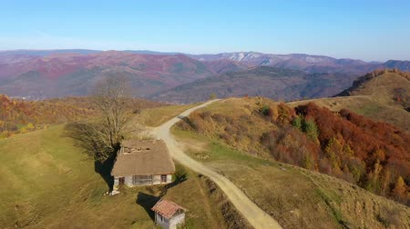 домик : Aerial drone 4k view of autumn countryside mountain landscape with wooden houses, thatched roof and dirt road in Transylvania, Romania Стоковые видеозаписи