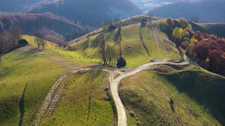 assombro : Aerial drone 4k view of autumn countryside mountain landscape with wooden houses, thatched roof and dirt road in Transylvania, Romania Vídeos