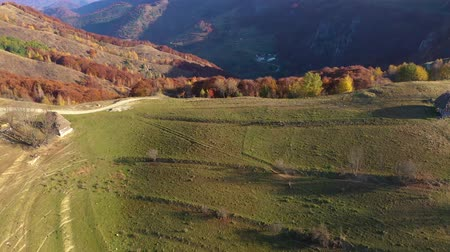 transilvânia : Aerial drone 4k view of autumn countryside mountain landscape with wooden houses, thatched roof and dirt road in Transylvania, Romania Stock Footage