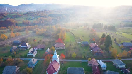 Трансильвания : Aerial 4k drone video of countryside village in Transylvania, Romania. Sunset over orthodox church