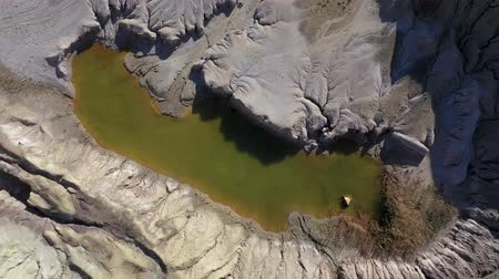 minerály : Aerial drone 4k movie of abandoned and flooded open pit gypsum mine, quarry. Polluted lake and mud. Industrial landscape