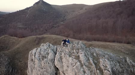 transilvânia : Hiking couple relaxing on a mountain peak. Aerial 4k drone movie