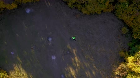 ヘルメット : Aerial 4k drone view of a cyclist lying down and resting in a forest lawn 動画素材