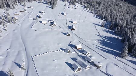 lodge : Snow covered remote village, homestead in the mountains. 4K aerial drone view
