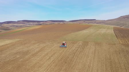 harvesting : 4k Aerial top view of a tractor, combine harvester plowing agricultural land in the spring