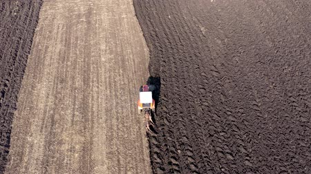 4k Aerial top view of a tractor, combine harvester plowing agricultural land in the spring