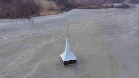 Ecological catastrophe, 4k aerial drone view of flooded and abandoned church in the middle of a lake contaminated with cyanide from a copper mine. Geamana, Romania