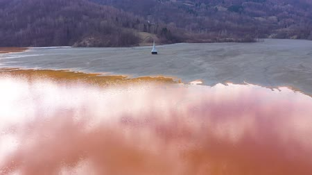 Flying over chemical waste, water polluted with contaminated mining residuals from a copper mine, abandoned church buried under toxic cyanide liquids mixing into lake. 4k Aerial drone view,  ecological catastrophe Стоковые видеозаписи
