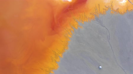 медь : 4k Aerial drone view of contaminated water with cyanide mixing into artificial lake, orange toxic residuals from a copper mine flooding the natural environment, ecological catastrophe