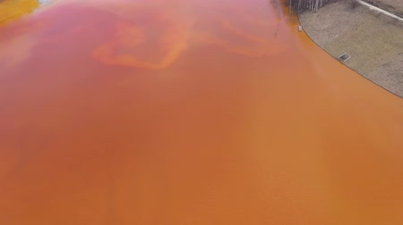 waste water : 4k Aerial drone view of contaminated water with cyanide mixing into artificial lake, orange toxic residuals from a copper mine flooding the natural environment, ecological catastrophe