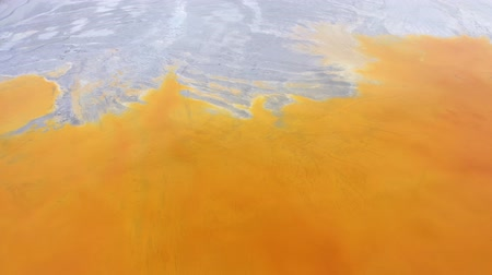 ekolojik : 4k Aerial drone view of contaminated water with cyanide mixing into artificial lake, orange toxic residuals from a copper mine flooding the natural environment, ecological catastrophe